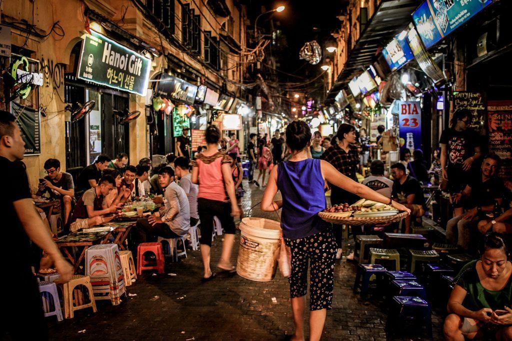 Eine belebte Straße in Hanoi, Vietnam mit vielen Restaurants und Leuten